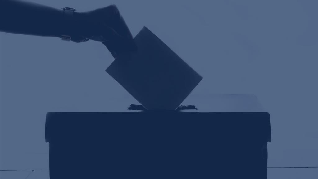 Osoba ubacuje listić u kutiju